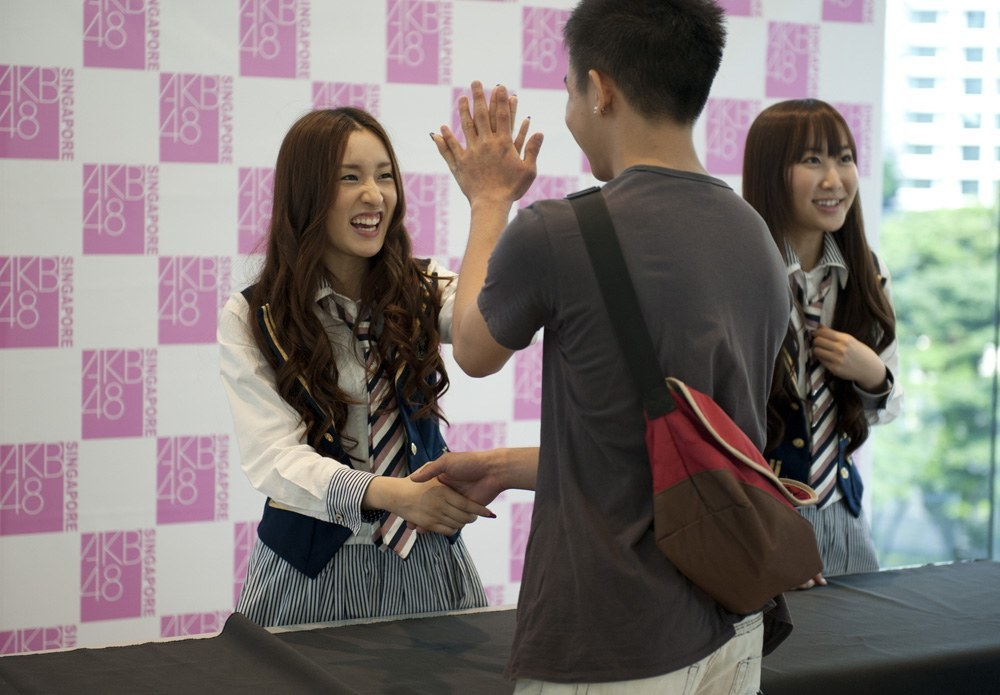 "An AKB48 fan meets one of his idols at a ""handshake event"". These events were cancelled earlier in 2014 after two band members were attacked by a man wielding a saw at one of the events. The girls sustained minor injuries and the events were resumed with increased security in July."