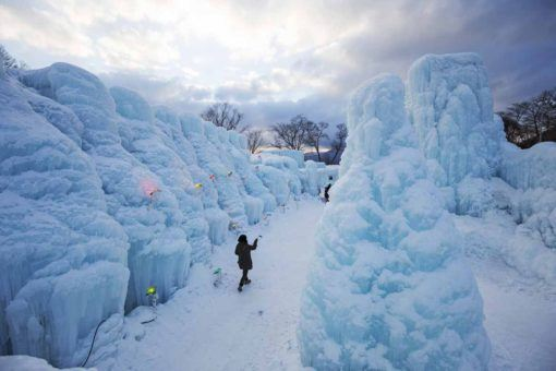 Lone person walking amidst ice structures